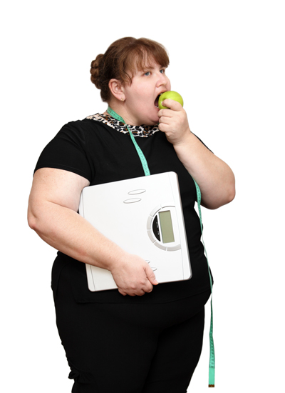 Overweight woman with scales and apple