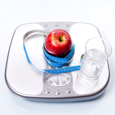 Weight scale, apple and glass of water