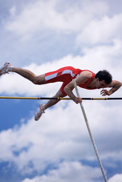 Man in mid air doing pole vault